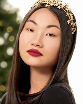 Weibliches Model mit glattem brünetten Haar und goldfarbenem Haarreif