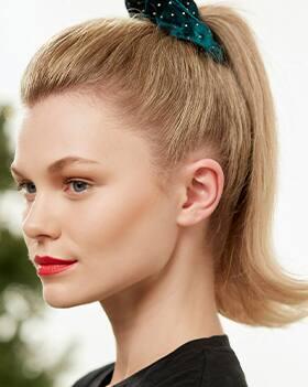 Weibliches Model mit blondem Haar und hohem Zopf mit grünem Haargummi